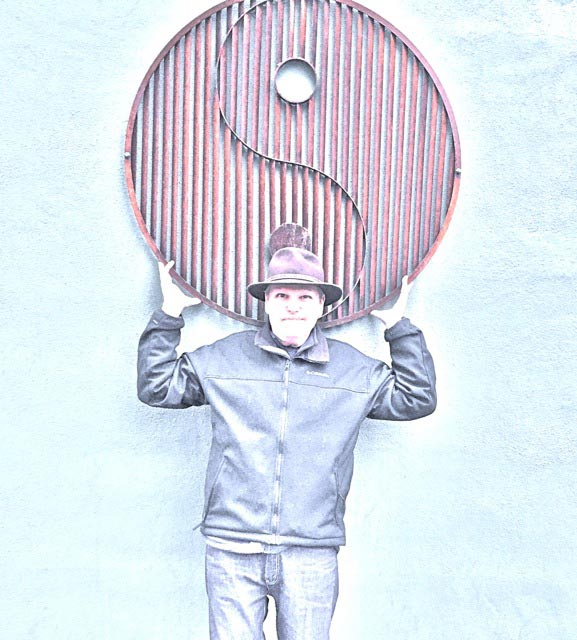 Dennis Freese posing under yin yang sign